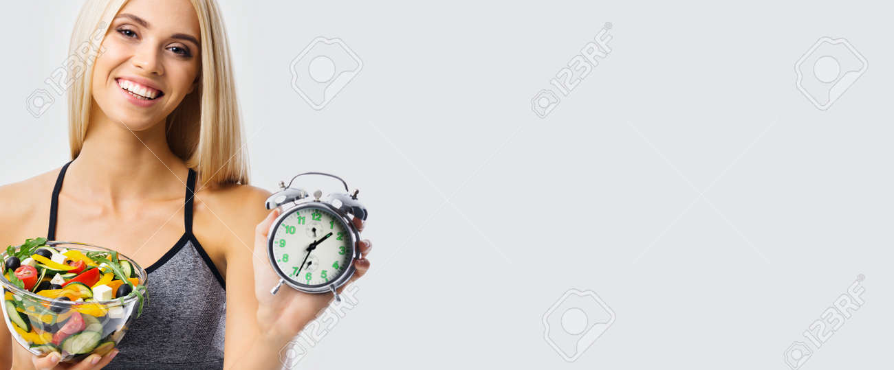Woman with alarm clock and greece salad with vegetables and cheese, over grey background with copy space. Girl in dieting, loss weight and time interval concept. Wide. - 171779204