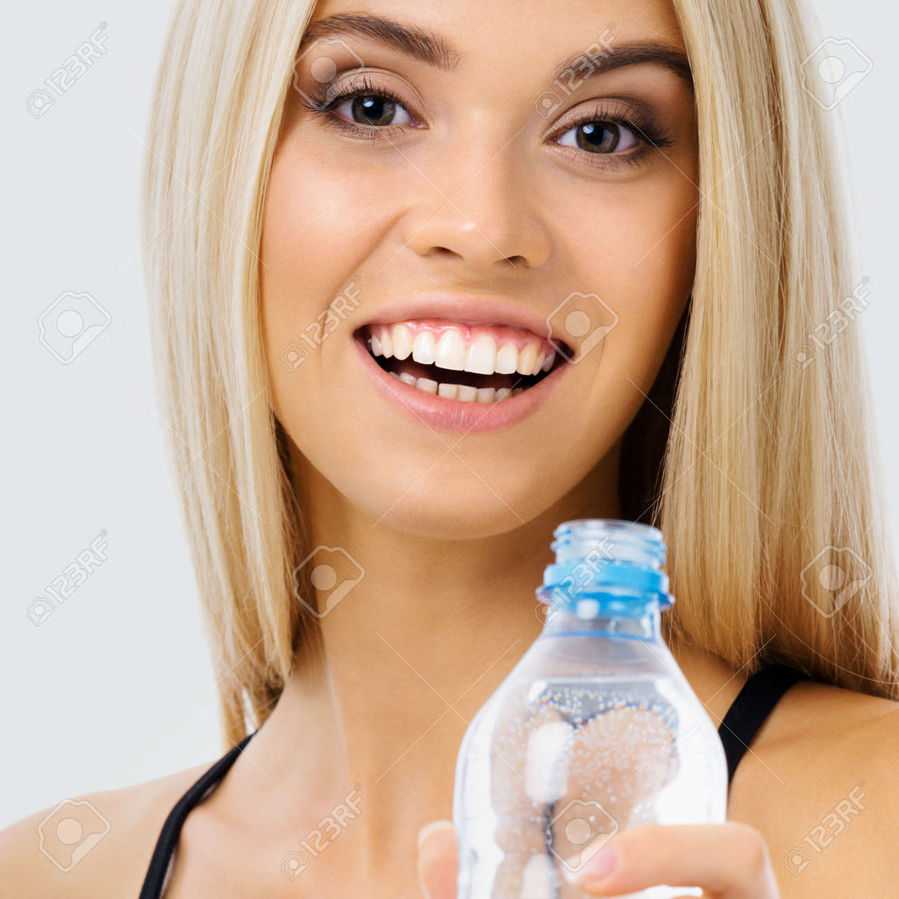Image of happy smiling young blond woman with bottle of water, over grey background. Female fitness instructor or personal trainer at studio shot. Health, beauty and fitness concept. - 171730380