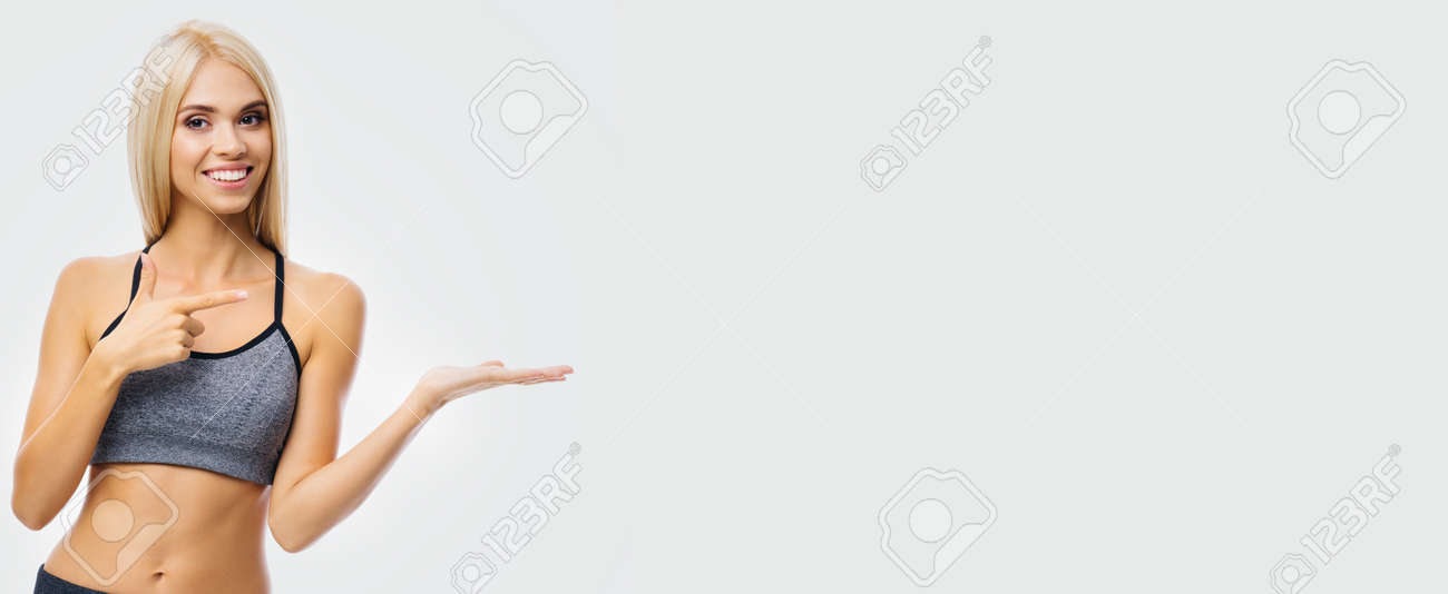 Beautiful smiling woman in sportswear showing, advertising, holding or giving some product or copy space area for text, over grey. Blond girl in fitness studio concept. Wide banner composition image. - 171730294