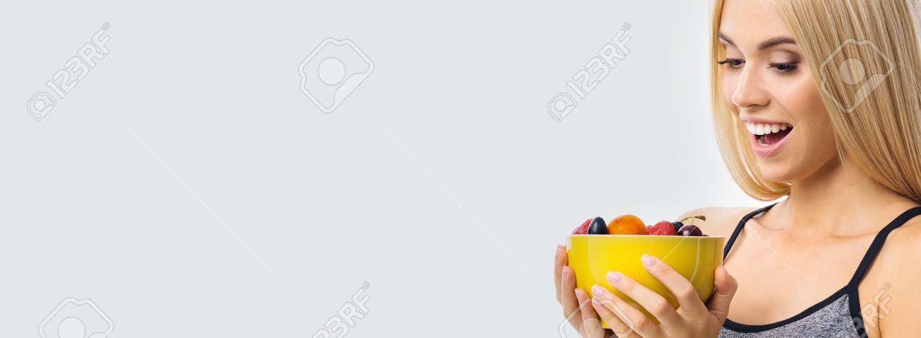 Image of happy excited woman holding yellow bowl plate of fruits, over grey background with copy space. Beautiful blond amazed smiling girl in dieting, loss weight and fitness concept. - 171730467