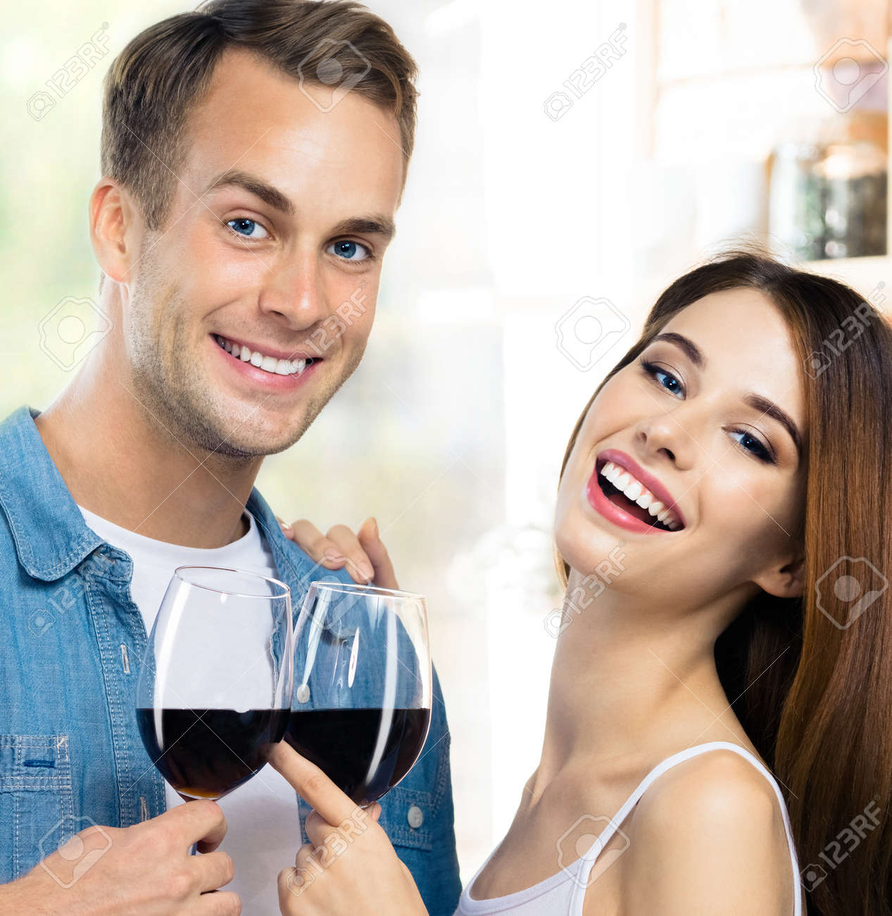 Attractive smiling young couple drinking redwine. Portrait image of caucasian models with red wine glasses in love concept. Man and woman posing together indoor. Square composition. - 171776887