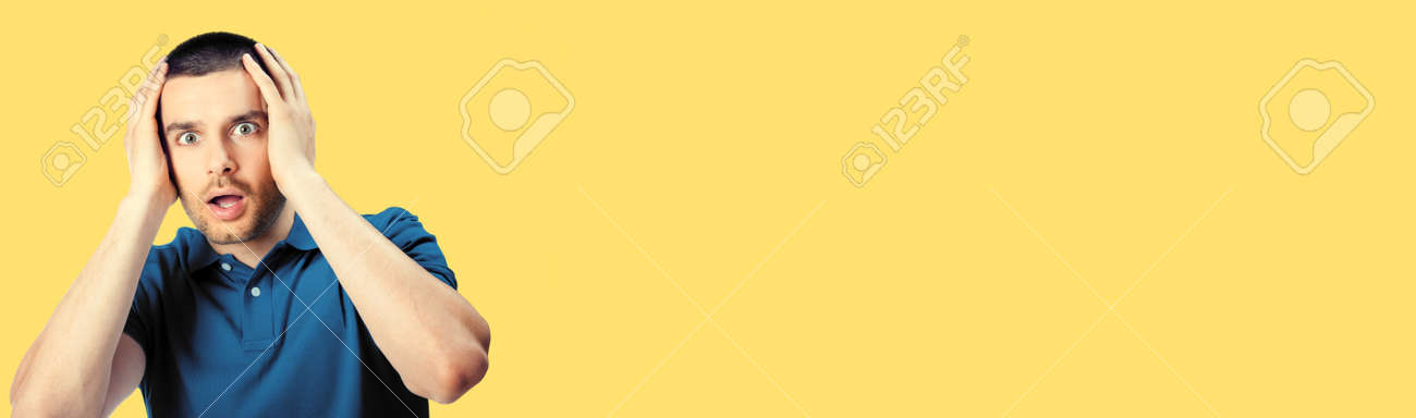 Unbelievable bad terrible news! Unhappy shoked panic man, isolated over yellow colour background. Emotions and unsuccess concept. Excited male model with rise up hands, blue casual cloth at studio. - 172034684