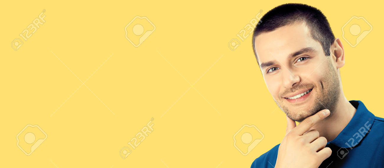 Portrait of happy smiling young man, isolated over yellow colour background. Male caucasian model in blue casual cloth at studio. Copy space area place for text. - 172034686