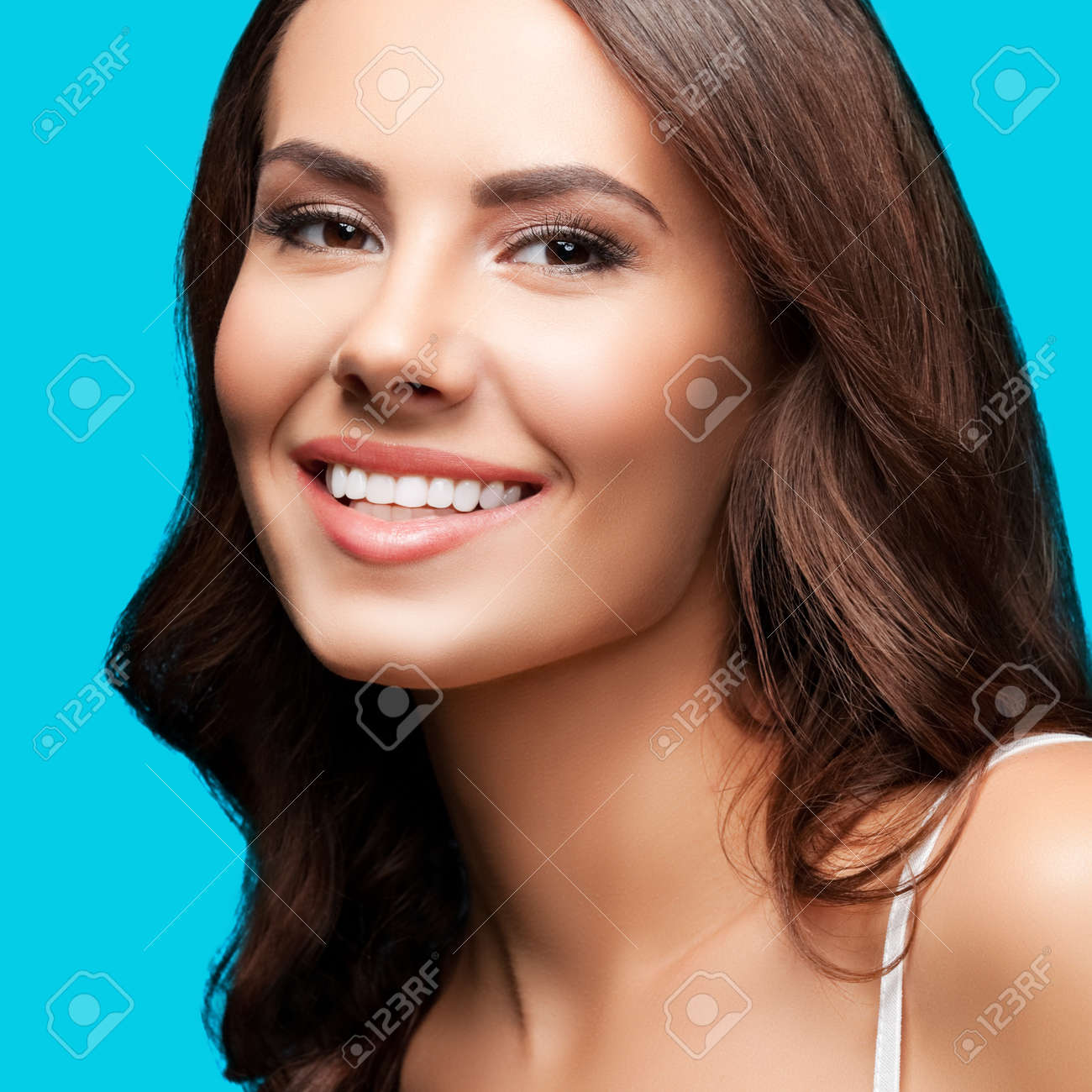 Portrait of smiling beautiful woman in white casual tank top, over aqua blue green background. Brunette girl at studio concept. Square composition. - 171953677