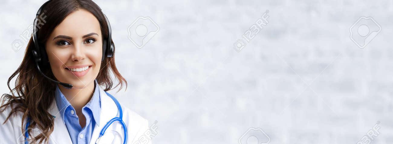 Happy smiling female doctor in headset, on white brick loft wall background, with copy space area. Medical contact call center concept. - 171998744