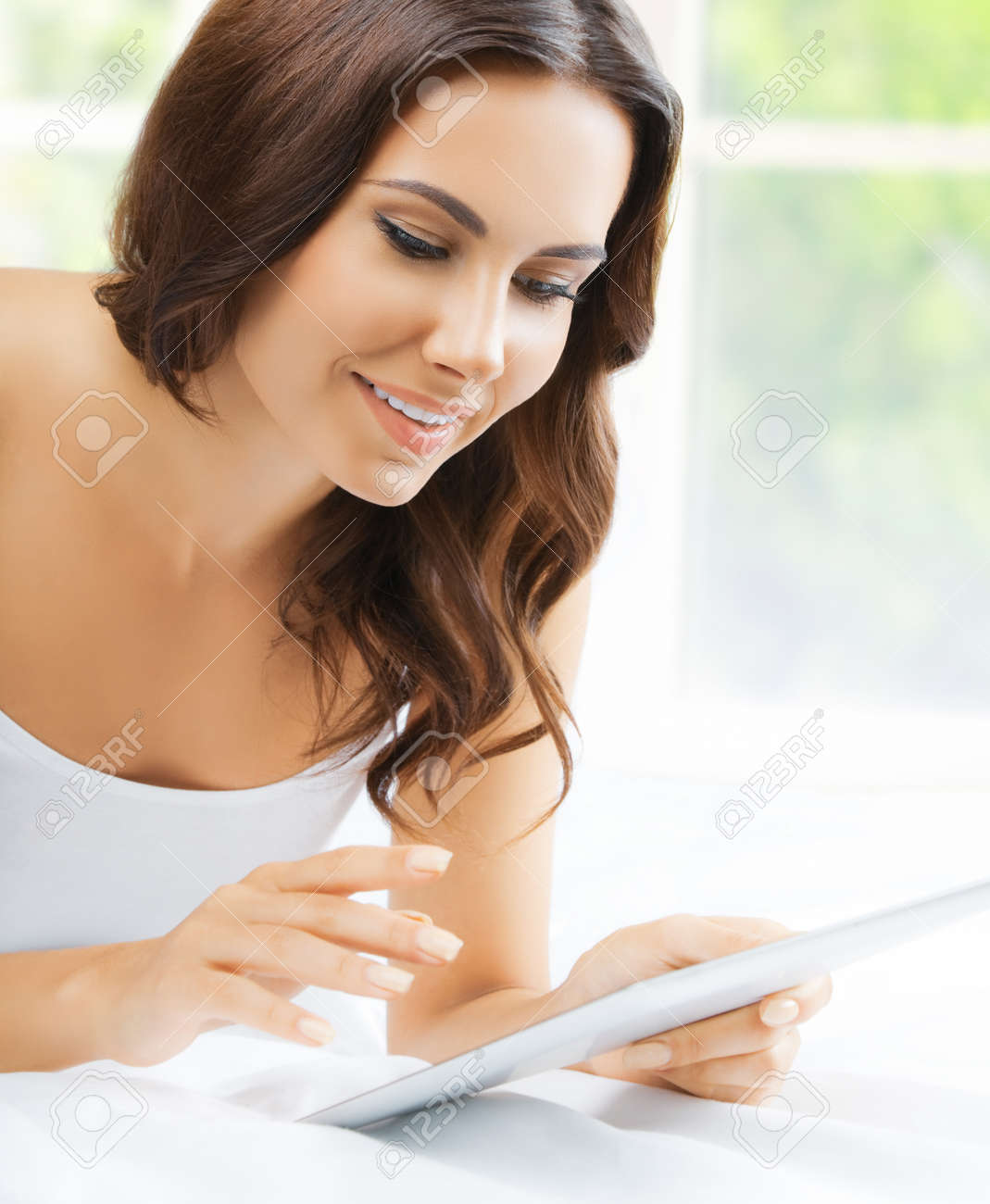Image of beautiful happy smiling amazed woman using tablet pc, touchpad, looking at, in bed room, near window. Attractive brunette girl at home bedroom. - 172034695
