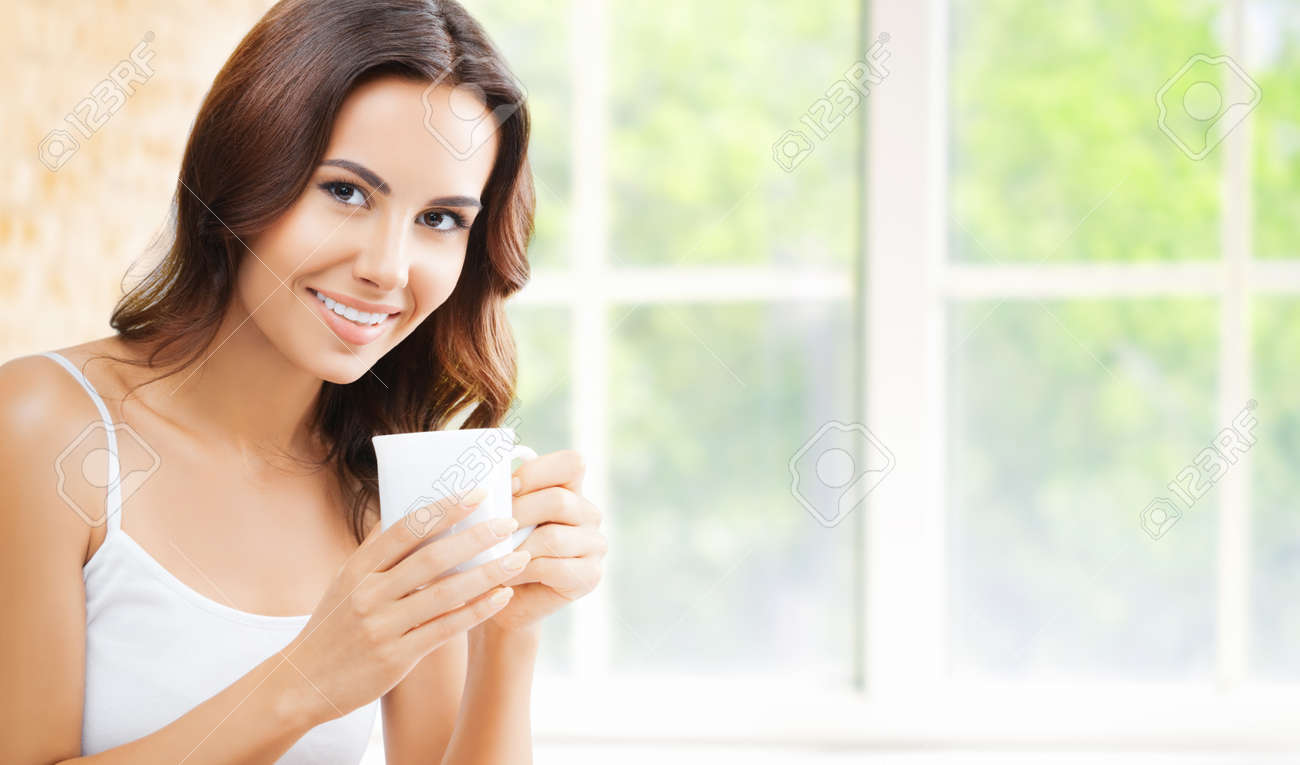 Portrait of happy smiling brunette woman in white lingerie top holding mug cup, drinking coffee or tea, at home, near window and loft style wall. - 172032726