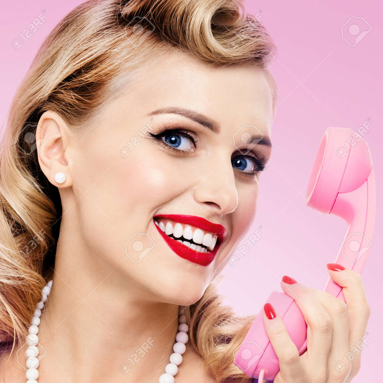Woman with phone, in pin up style dress, showing blank signboard with copyspace area, on pink background. Blond model posing in retro fashion and vintage studio concept. Square. - 172418472