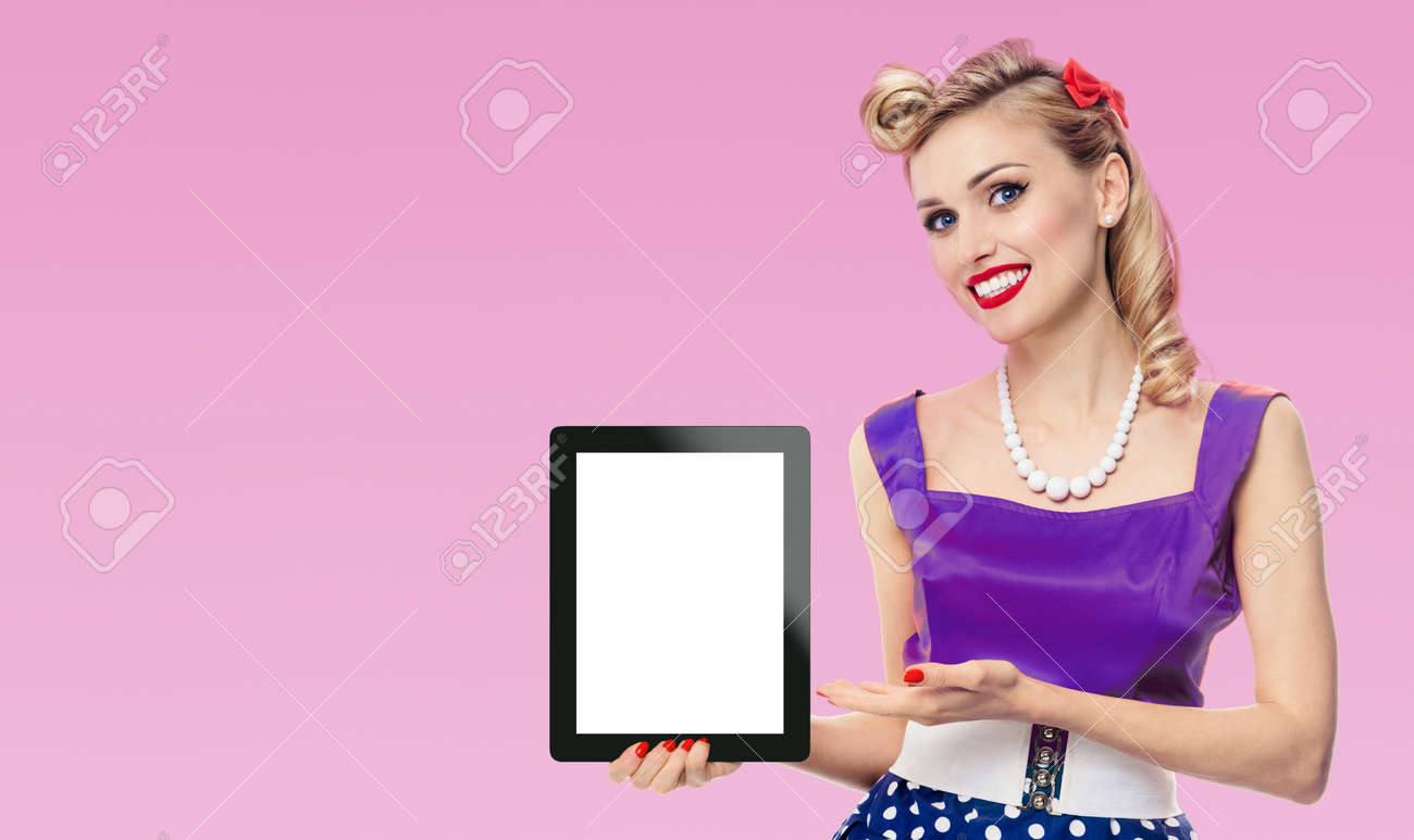 Woman showing blank tablet pc monitor, with copy space, dressed in pin up style dress in polka dot, pink background. Blond model posing in retro fashion vintage concept. - 172155554