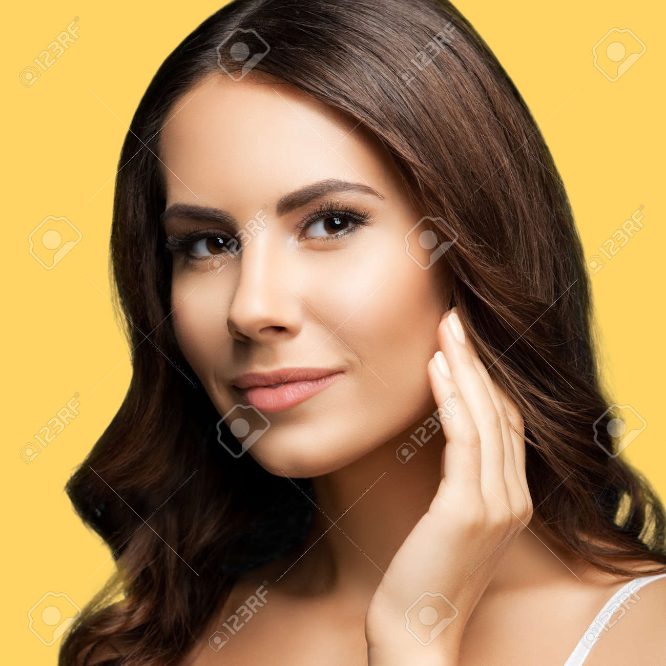 Portrait of beautiful woman in white casual tank top, over yellow color background. Brunette girl at studio beauty concept. Square composition image. - 172264321