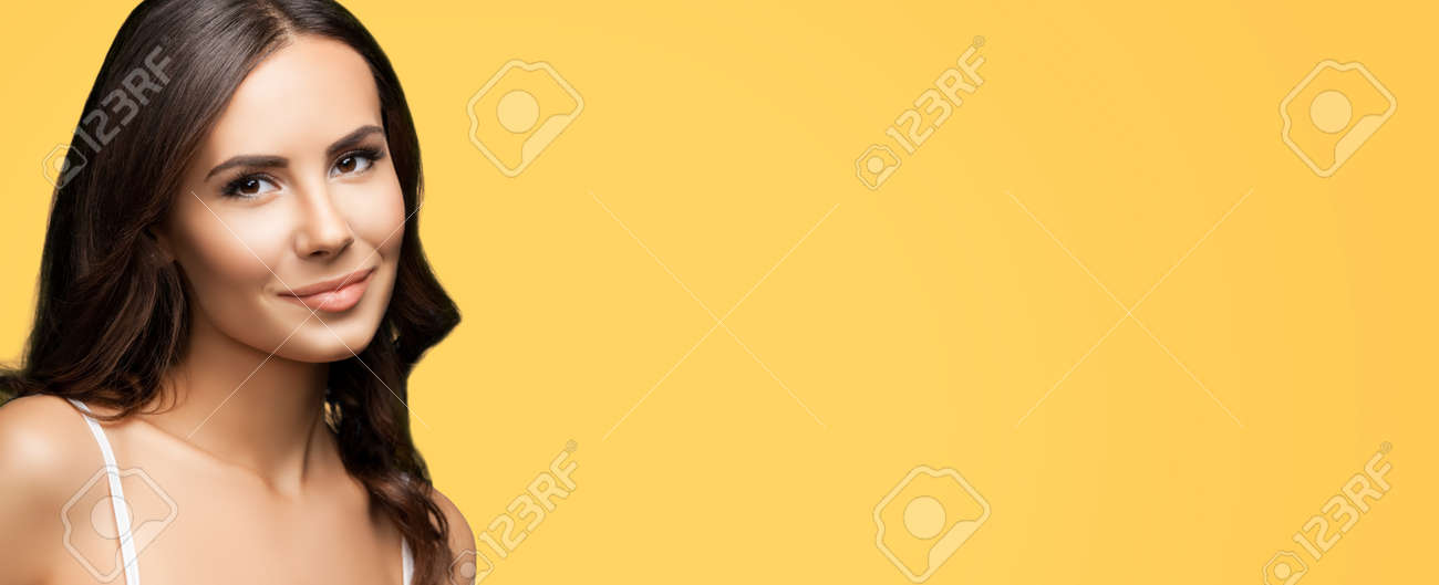 Portrait of happy smiling beautiful woman in white casual tank top, over yellow color background. Brunette lovely girl at studio beauty fashion concept. Wide horizontal composition image. - 172264542