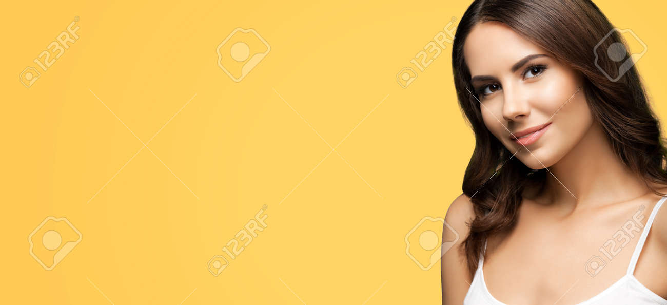 Portrait of happy smiling beautiful woman in white casual tank top, over yellow color background. Brunette girl at studio. Beauty concept. Wide horizontal composition image with copy space. - 172264606
