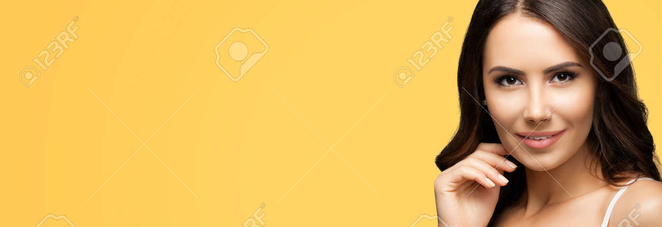 Portrait of smiling beautiful woman in white casual tank top, over yellow color background. Brunette girl at studio beauty fashion concept. Wide horizontal banner composition. - 172264353