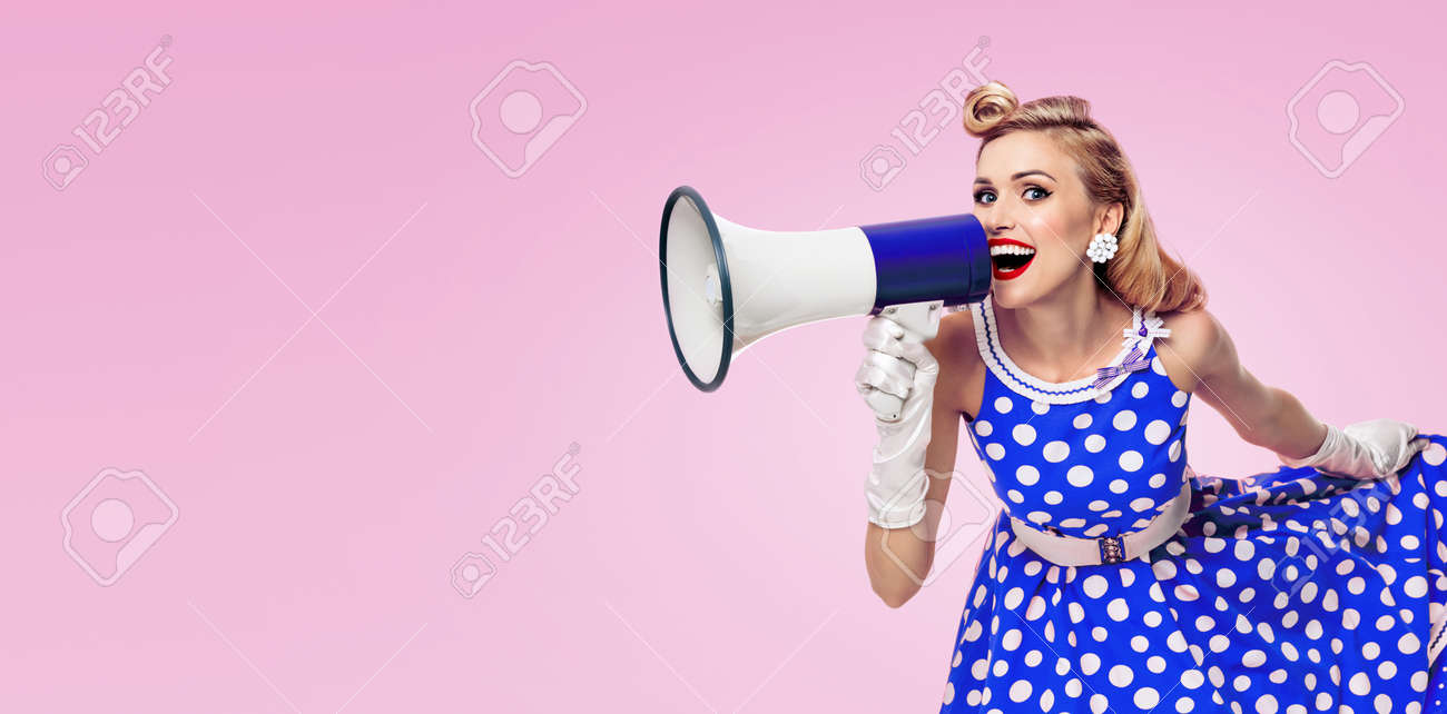 Image of woman holding megaphone, dressed in pin up style blue dress in polka dot white gloves, over pink colour background. Female blond model posing in retro fashion vintage studio concept. - 172447143