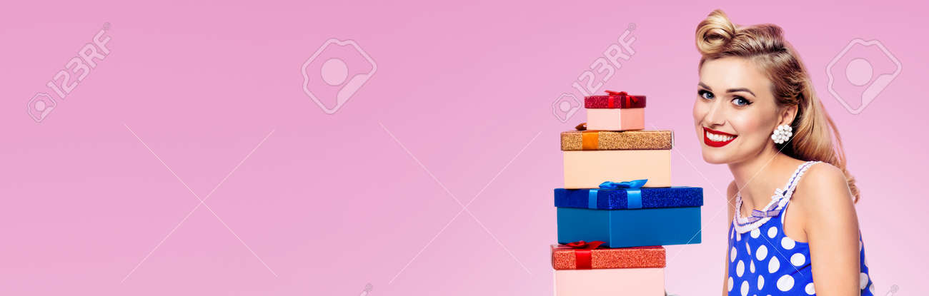 Studio image of smiling woman in pin up style blue dress in polka dot white gloves, holding gift boxes, over pink background. Model posing in retro fashion and vintage shoot. Wide. - 172447145