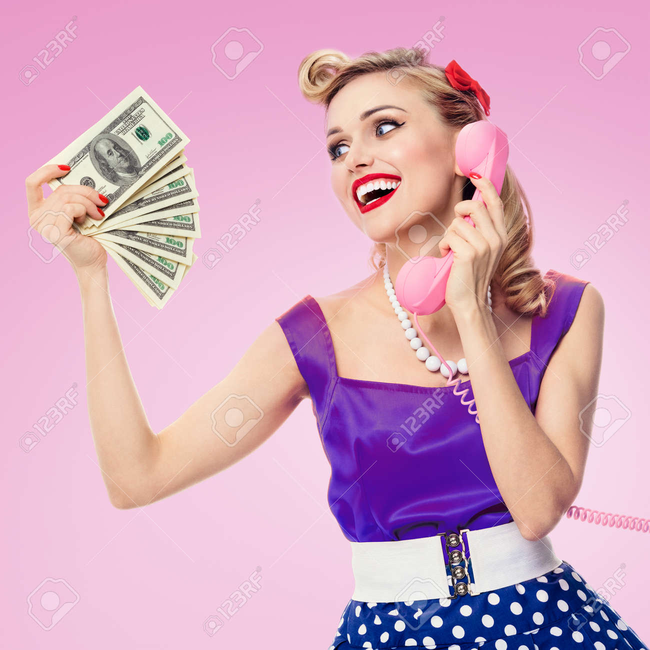 Image of happy woman with money, talking on phone, pin-up style dress in polka dot, over pink background. Caucasian blond model posing in retro fashion and vintage studio shoot. - 172447146