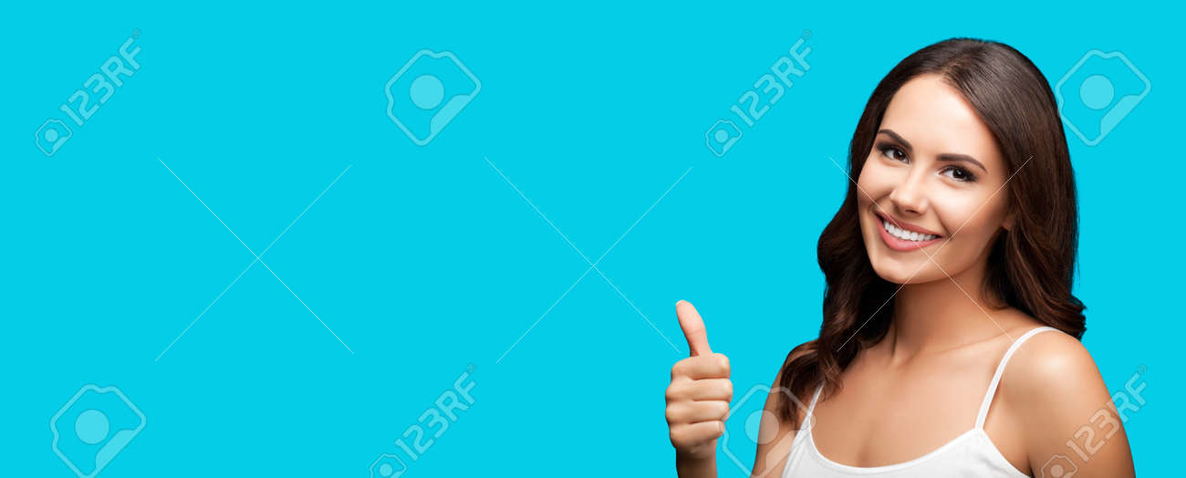 Photo of woman showing thumb up hand sign or like gesture, isolated on aqua blue green color background. Portrait of happy smiling gesturing brunette girl at studio. Wide horizontal banner composition - 172410064