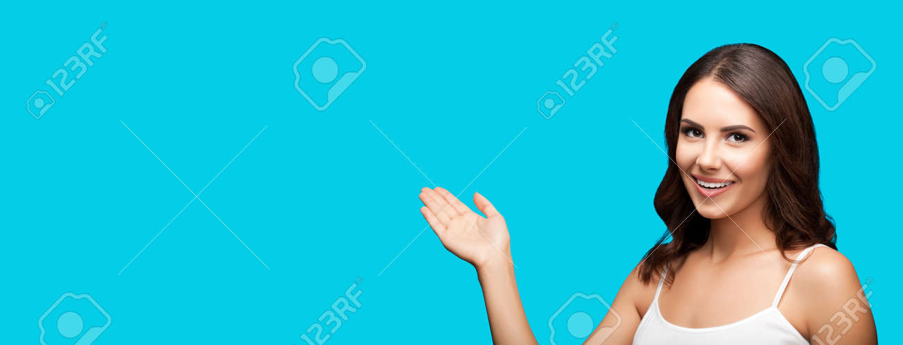 Photo of smiling beautiful woman in white casual wear holding hand with flat palm, showing, giving, advertising some product or copy space for ad text. Aqua blue green colour background. Brunette girl - 172409880