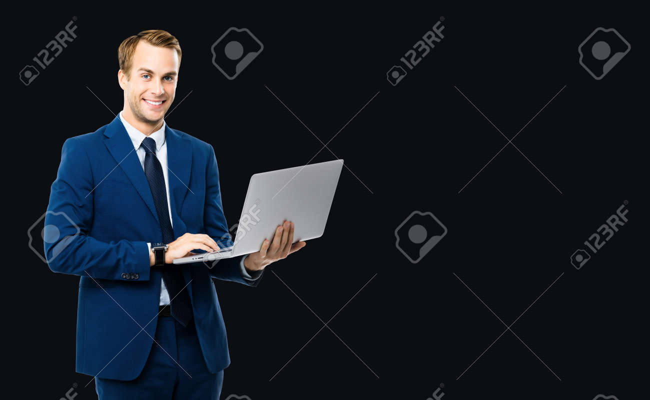 Photo of happy smiling businessman working with laptop, isolated over black color background. Business man in blue confident suit and tie, with notebook in studio concept. - 172447156