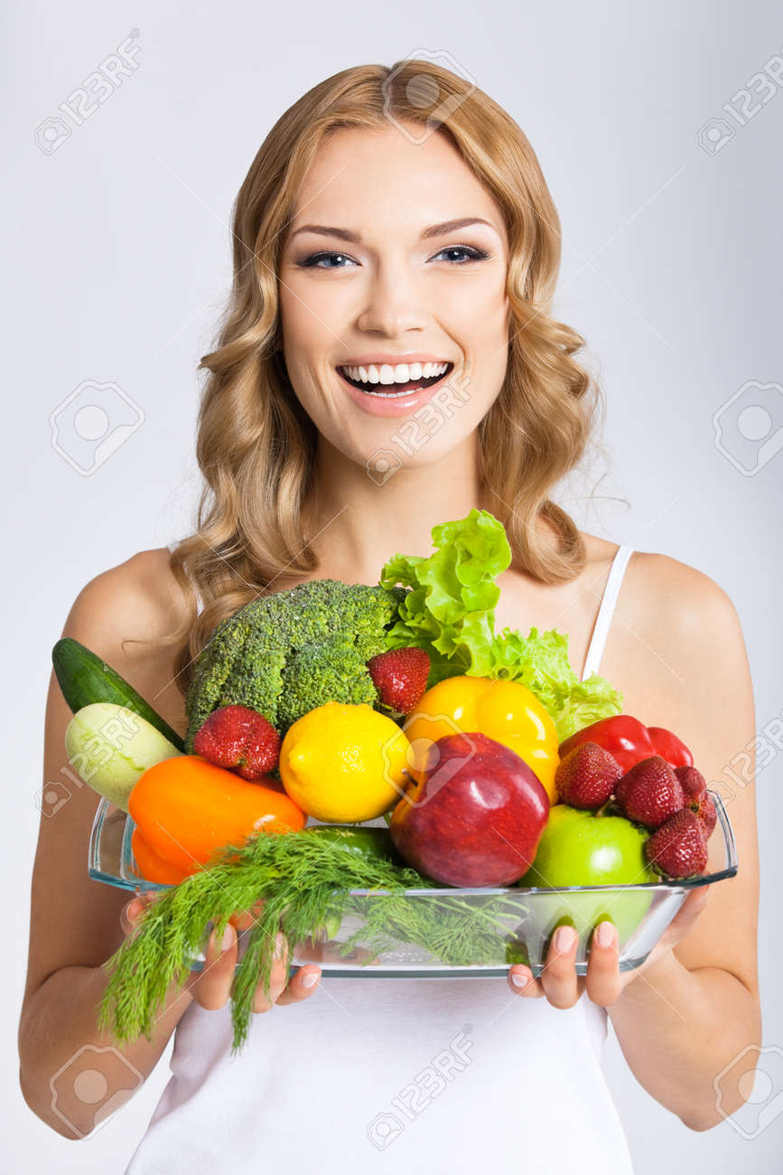 Portrait photo of happy smiling young beautiful woman with healthy vegetarian raw food, over gray background. Attractive blond girl at studio. - 172447160