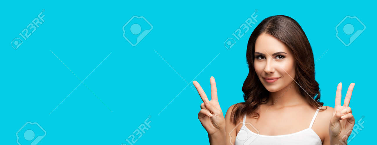 Photo of woman showing two fingers or victory hand sign gesture, isolated on aqua blue green color background. Portrait of happy smiling gesturing brunette girl at studio. Wide banner composition. - 172479798