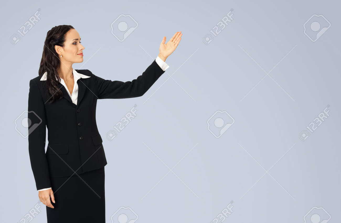 Photo image of happy smiling woman in black confident suit, showing at copy space. Business concept. Isolated over grey background. Brunette businesswoman. - 172480060