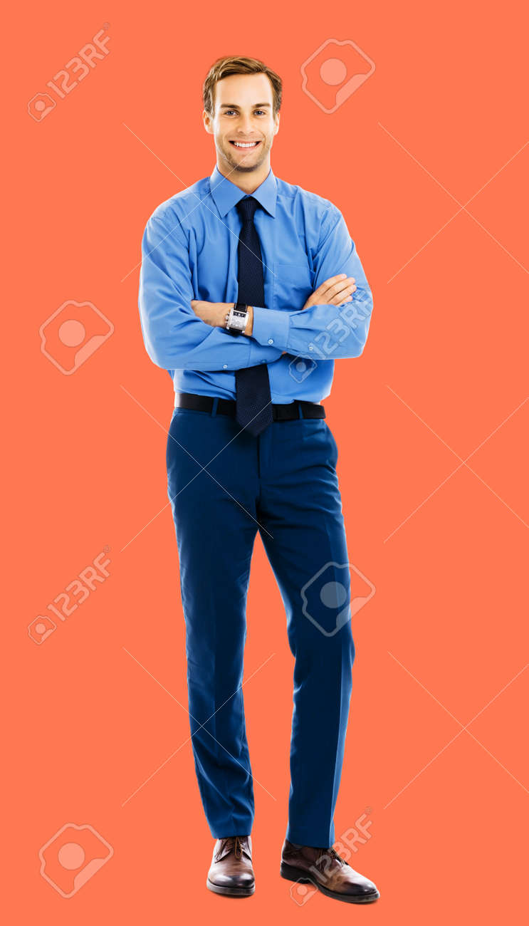 Full length body portrait of happy smiling businessman in blue cloth, standing in crossed arm pose, isolated over bright vivid orange color background. Confident business man at studio image. - 172491047