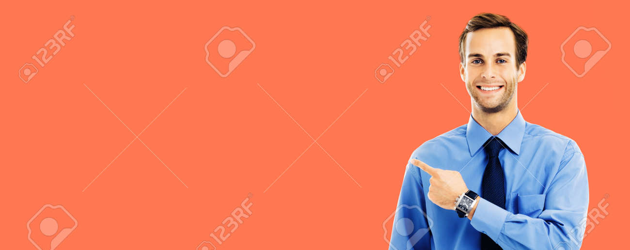 Portrait of confident businessman pointing showing something, isolated over bright vivid orange color background. Mock up copy space area. Success in business and education studio concept. - 172490831