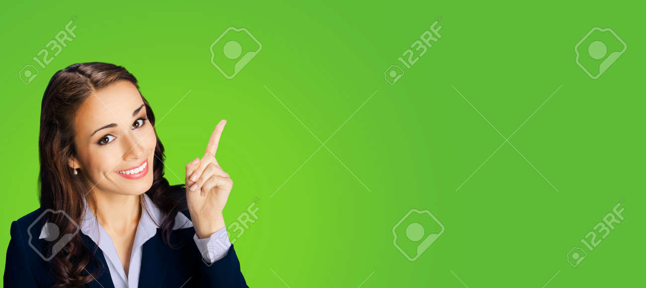 Photo of young happy smiling woman in black confident suit, showing pointing at mock up copy space for text. Business ad concept. Green color background. Wide horizontal image. - 172592559