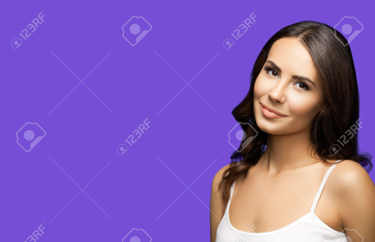 Portrait of happy smiling beautiful woman in white casual tank top, on violet purple background. Brunette lovely girl at studio beauty fashion concept. Wide horizontal composition image. - 172673585