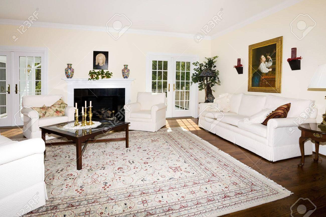 Lussuoso soggiorno con camino, tappeto orientale su legno piano ...