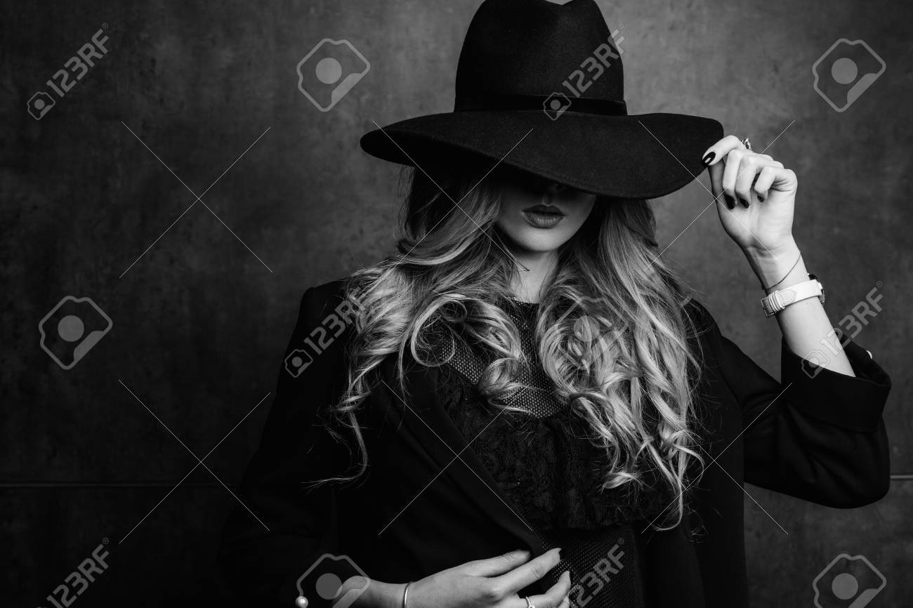 Beautiful young mysterious blond girl in black hat and black jacket on gray background. Eyes are covered with a hat. Manicure - long red nails, nail polish. Fashion, beauty. - 95004580