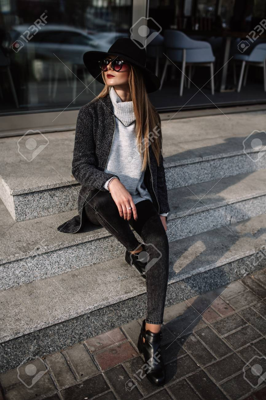 c116d78cc49b Street style. Women s fashion. Portrait of a young beautiful fashionable  girl wearing sunglasses. Model in a stylish black hat