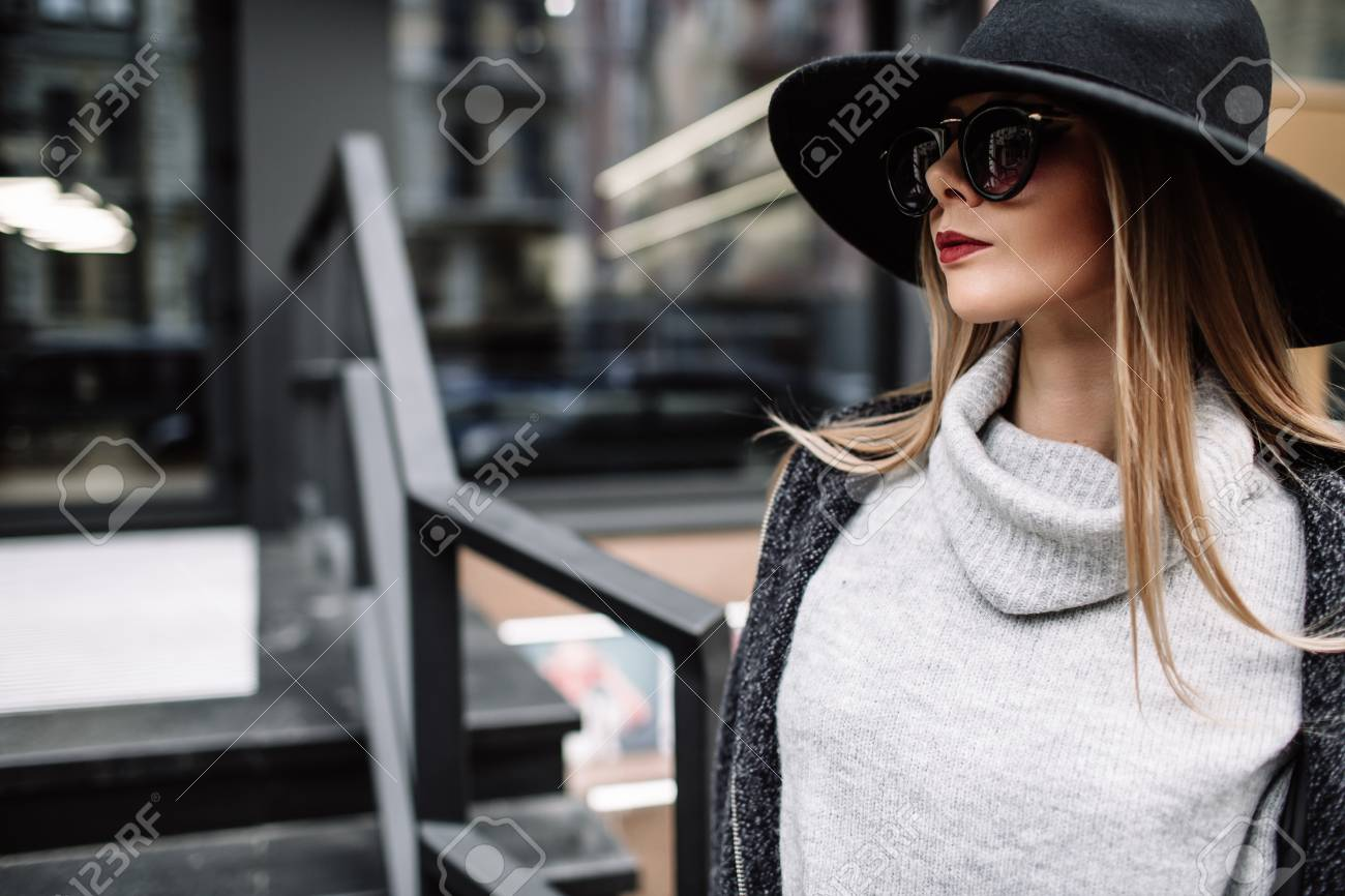 d24f6932aae Portrait of a young beautiful fashionable girl wearing sunglasses. Model in  a stylish black hat