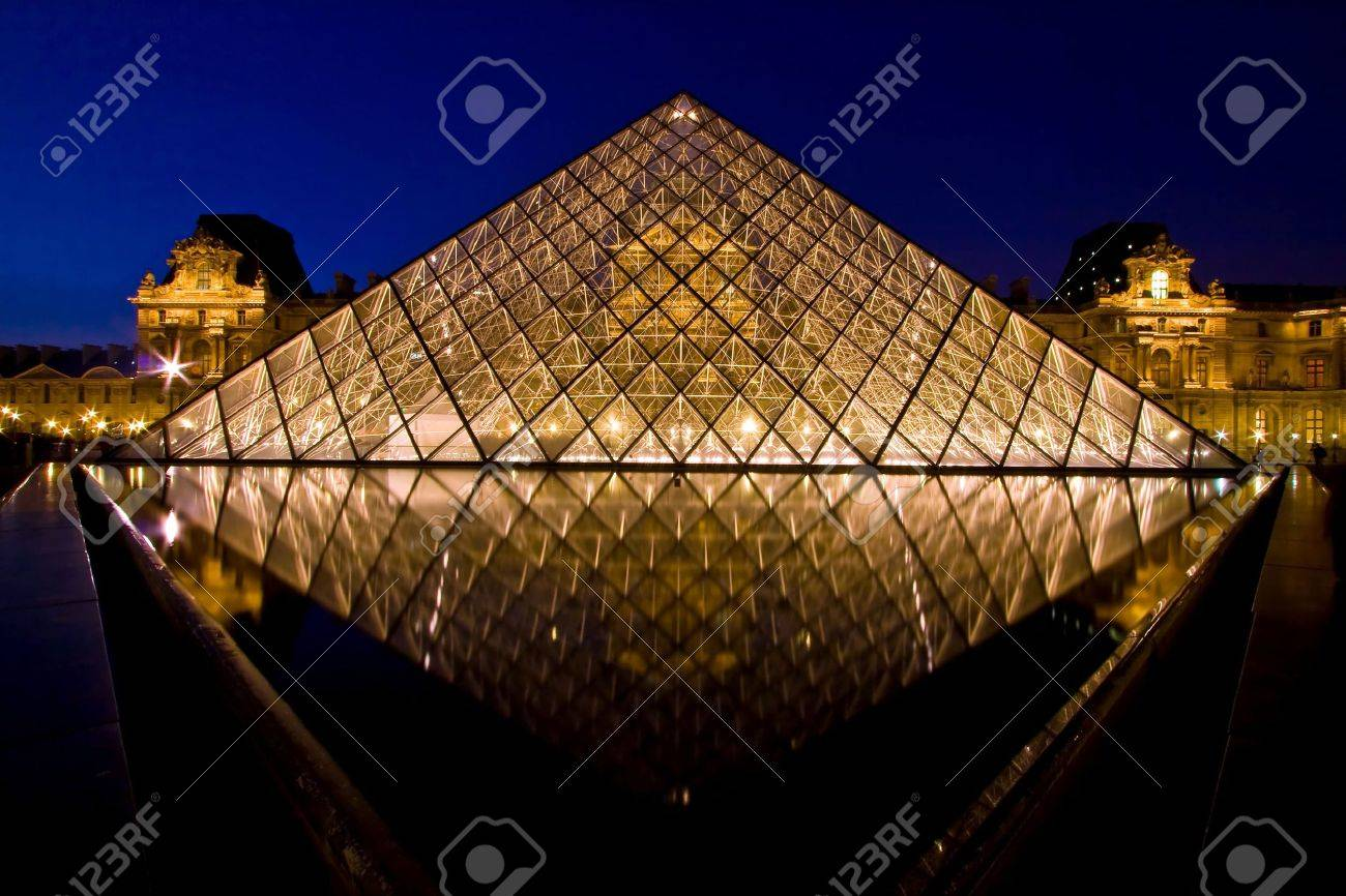 Paris France APR 16,2010 - Reflection of Louvre pyramid shines at dusk during the Summer Exhibition in Paris. This is one of the most popular tourist destinations in France. Stock Photo - 7665319