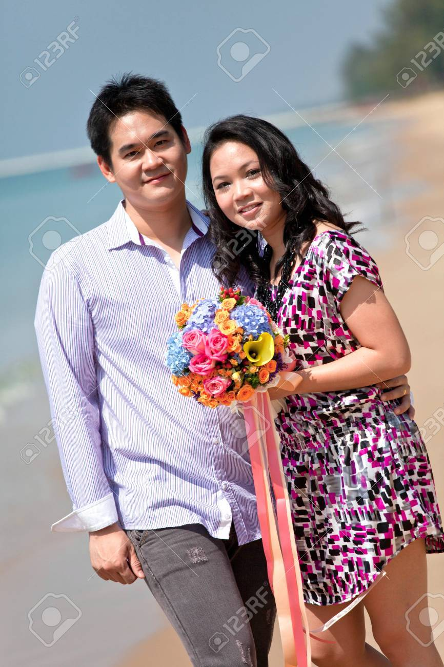 lovely young couple with flower bouquet standing on the beach Stock Photo - 8257852