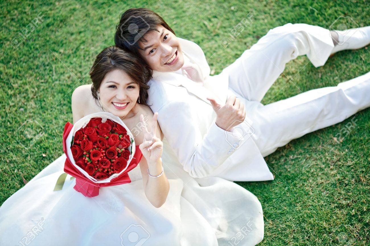 portrait of bride and groom sitting on fresh grass with rose bouquet Stock Photo - 11772307