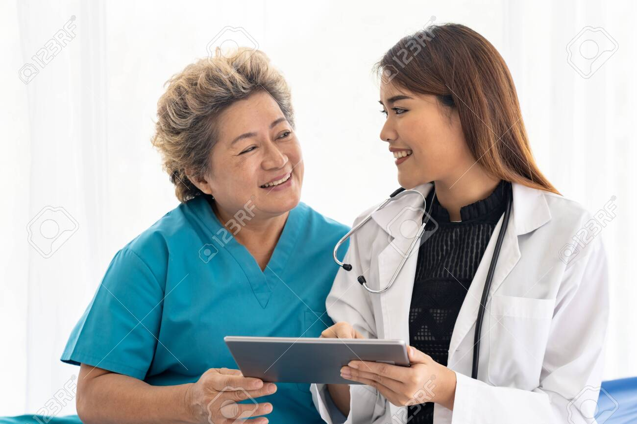 Asian confidence doctor using digital tablet expressing health concerns with old elderly woman patient sit on wheelchair - 136079244