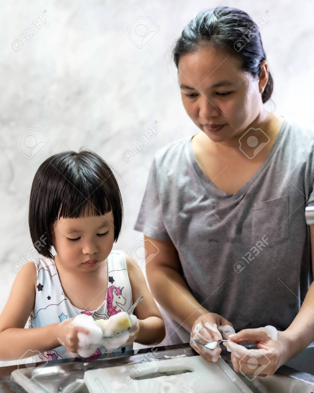 Asian girl washing dish and tableware with her mom, housework for child make executive function for kid. Houseworking for kid lifstyle and family concept. - 150854585