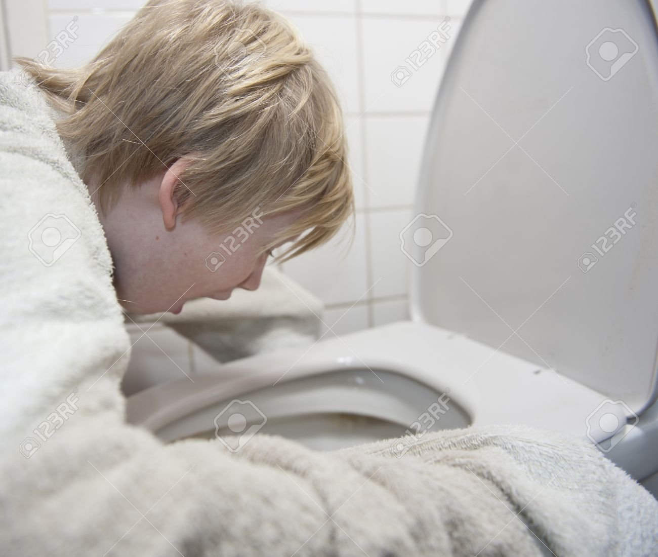 young boy and the toilets Stock Photo - Young boy with stomach flu vomiting in toilet