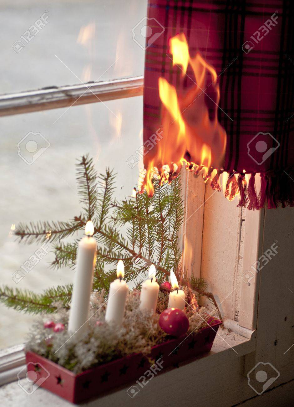 advent candle wreath setting fire on a curtain stock photo