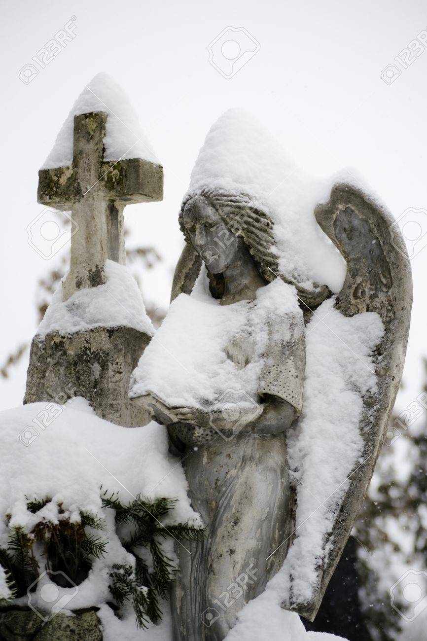 Close up of a stone angel statue covered with snow Stock Photo - 12185037