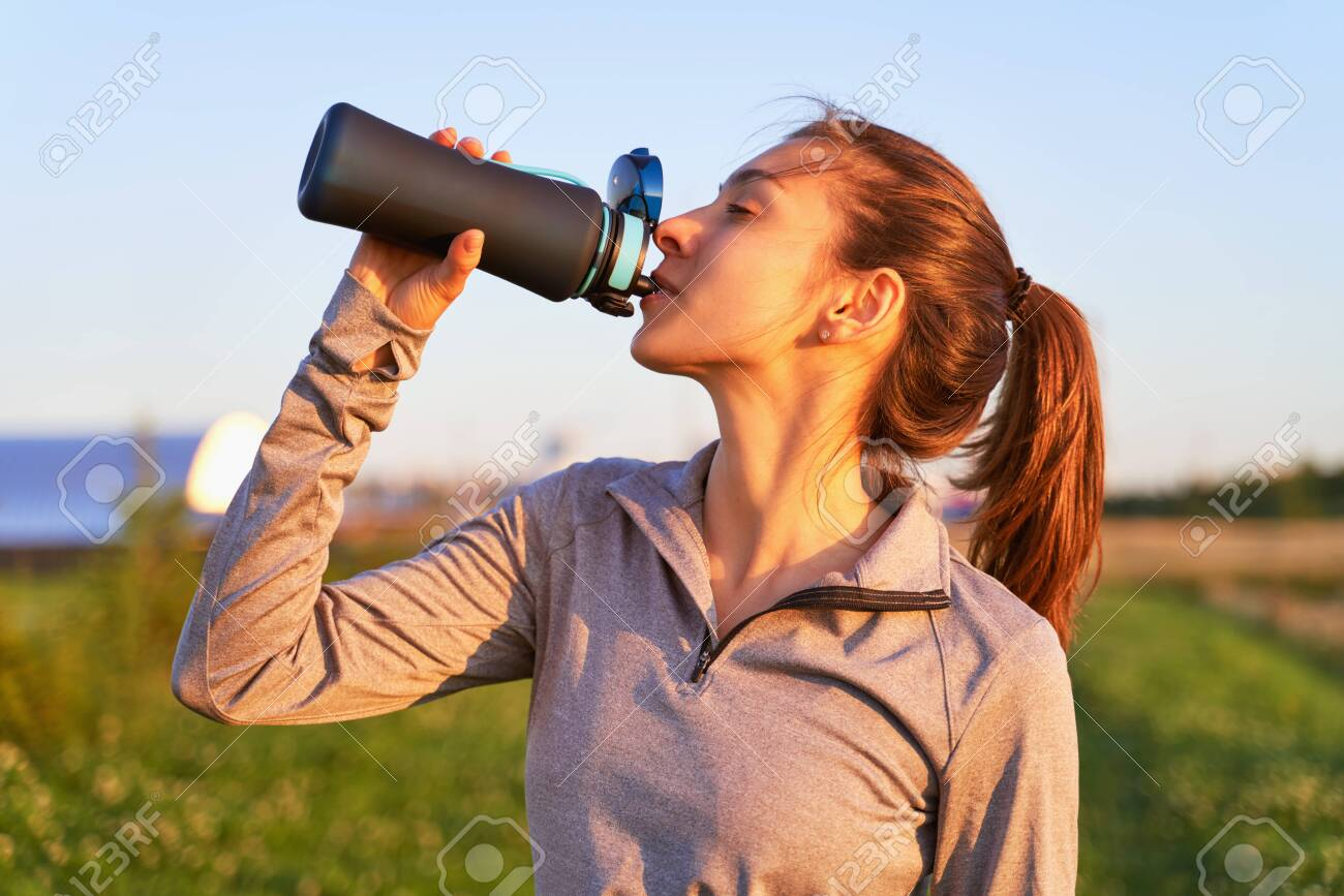 A young girl after workout drinking water - 130646383
