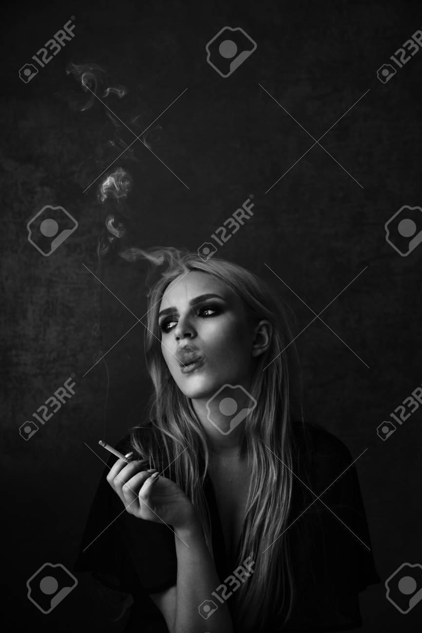 Sexy woman with smoky eyes makeup smoking black and white