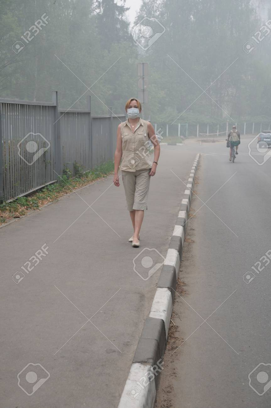 YUBILEINY, MOSCOW REGION, RUSSIA - AUGUST 6: Woman is walking down empty street in thick smog with a mask on her face August 6, 2010 in Yubileiny, Moscow region, Russia. Smog was caused by wildfires Stock Photo - 7537187
