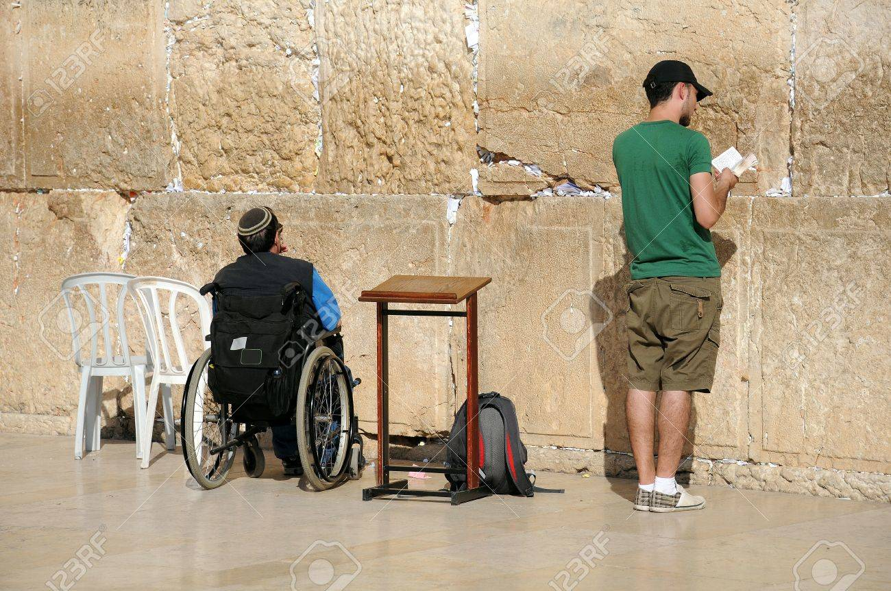 JERUSALEM, ISRAEL - NOVEMBER 10: A young Caucasian man and a handicapped person are praying at the Wailing Wall November 10, 2010 in Jerusalem, Israel.  Stock Photo - 8502257