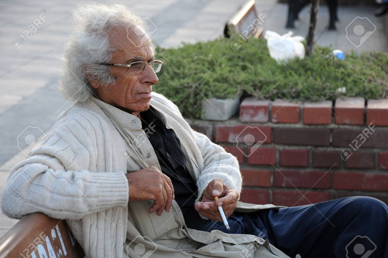 Senior Tirkish gray-haired man with a cigarette in the town of Kusadasi in Turkey on the 24th of September, 2009 Stock Photo - 9397080