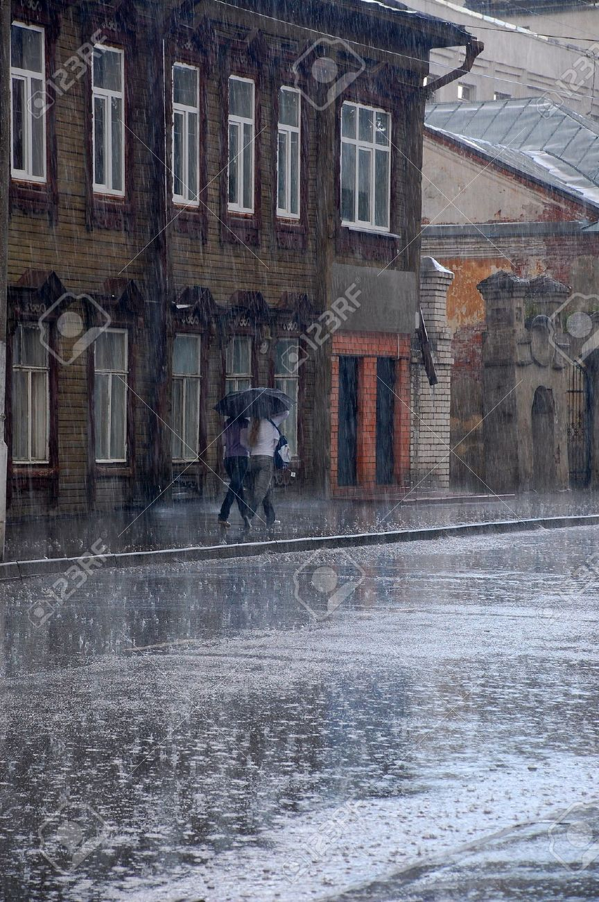 Two women walk in the rain down the street of the old Russian town Stock Photo - 16125826