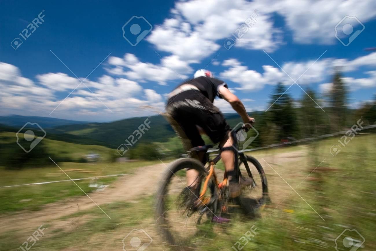 Male mtb biker during downhill event in motion blur - 1414745