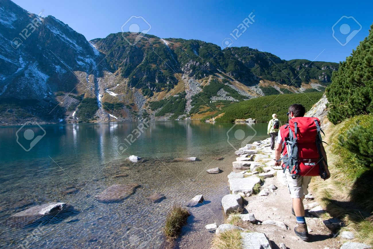 Couple trekking by the side of mountain pond in Tatra Mountains, Poland - 1727445